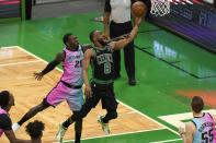 Boston Celtics' Kemba Walker (8) drives toward the basket as Miami Heat's Kendrick Nunn (25) tries to block in the second half of a basketball game, Sunday, May 9, 2021, in Boston. (AP Photo/Steven Senne)