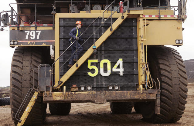 Michelle Noer climbs the steps to the world's largest dump truck at the Syncrude Aurora mine near Fort McMurray, Alberta, in this May 23, 2006 file photo. (REUTERS/Todd Korol/Files)