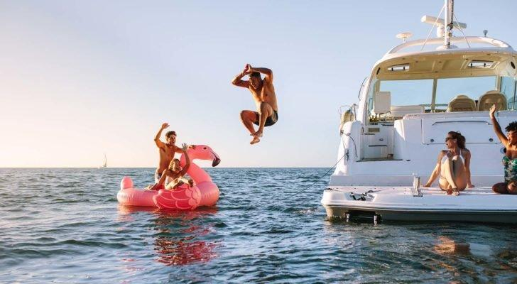 A person jumping off a boat into the water next to their friend who is floating on a flamingo-shaped float