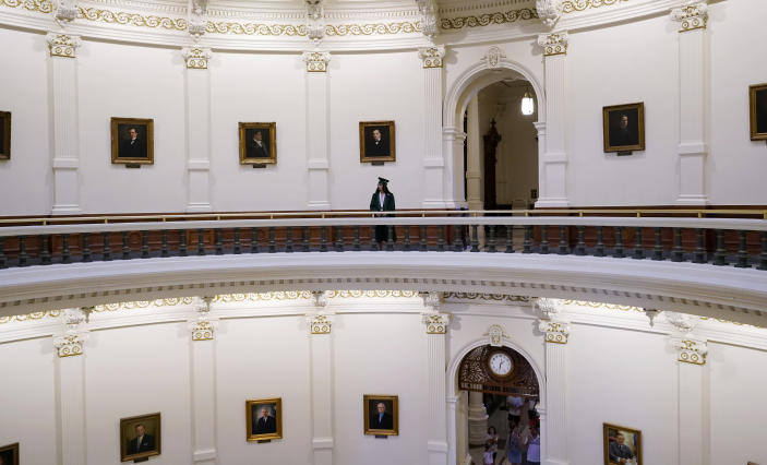 A graduate poses for family photos in the rotunda at the State Capitol, Tuesday, June 1, 2021, in Austin, Texas. The Texas Legislature closed out its regular session Monday, but are expected to return for a special session after Texas Democrats blocked one of the nation's most restrictive new voting laws with a walkout. (AP Photo/Eric Gay)