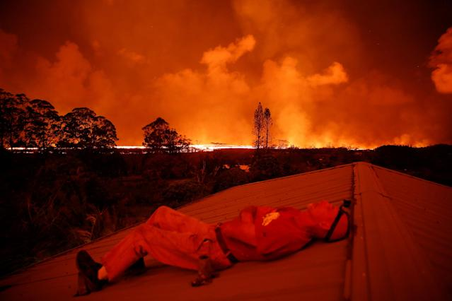 <p>Mark Clawson, 64, rests while watching a lava flow from a neighbor's roof on the outskirts of Pahoa during ongoing eruptions of the Kilauea Volcano in Hawaii, June 6, 2018. (Photo: Terray Sylvester/Reuters) </p>