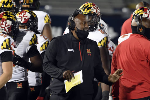 FILE - In this Saturday, Nov. 7, 2020, file photo, Maryland head coach Mike Locksley, center, talks with his players during a timeout late in the fourth quarter of an NCAA college football game against Penn State in State College, Pa. An outbreak of COVID-19 on the Maryland football team that resulted in a positive test for head coach Michael Locksley has caused the cancellation of Saturdays Big Ten game against Michigan State. (AP Photo/Barry Reeger, File)