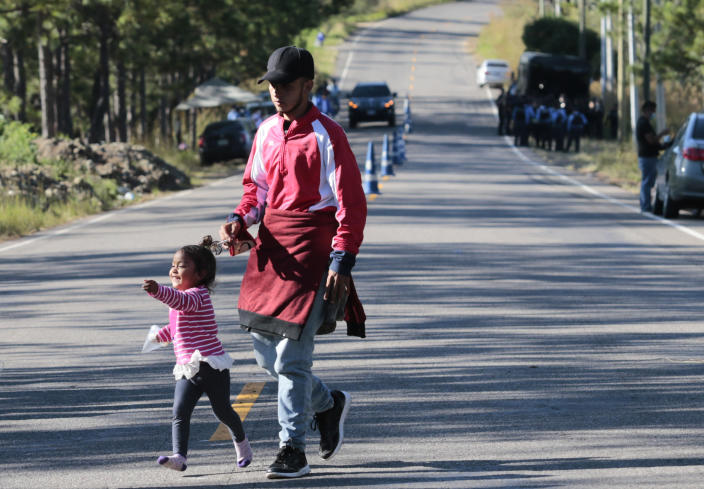 A migrant and his daughter walk near a police checkpoint on their way North near Agua Caliente, close to the border with Guatemala, Thursday, Dec. 10, 2020. Honduran security forces stationed on the highway a few kilometers before Agua Caliente, asked the migrants for their passports or identity cards and proof of a COVID-19 test, and if they did not produce those documents they would not be allowed to move on. (AP Photo/Delmer Martinez)