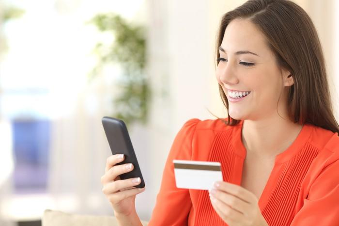 A woman smiles at her smartphone, holding a credit card in her other hand.