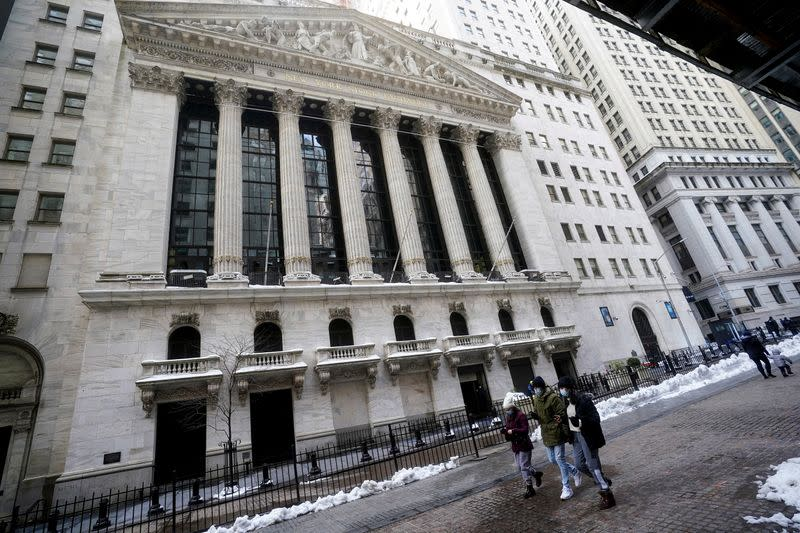 People walk past the New York Stock Exchange in New York City