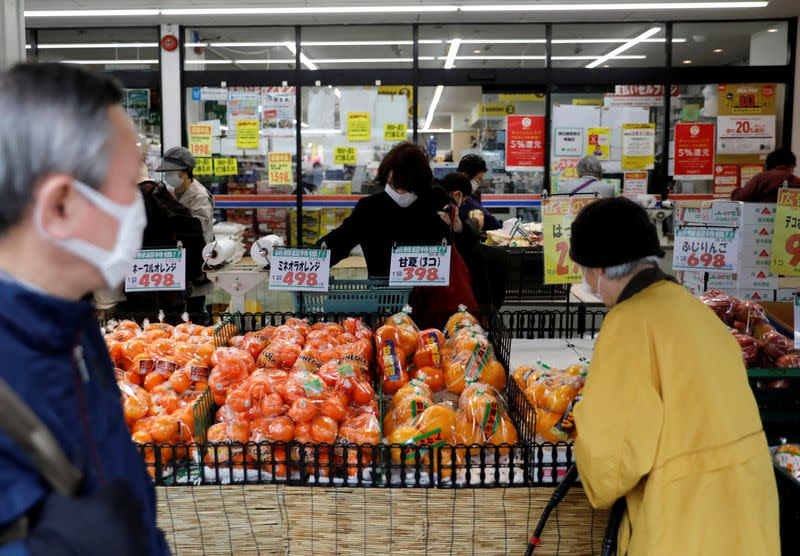 Shoppers wearing protective face masks, following an outbreak of the coronavirus disease, are seen at a supermarket in Tokyo, Japan