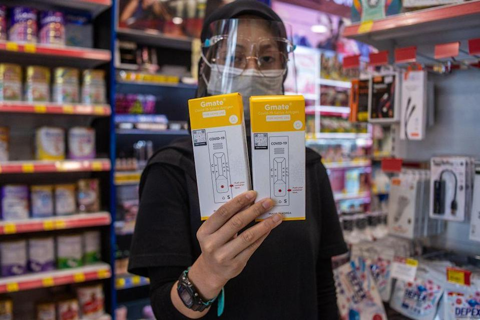 A pharmacy staff holds up the Gmate Covid-19 rapid antigen self-test kits in Subang Jaya July 28, 2021. — Picture by Shafwan Zaidon