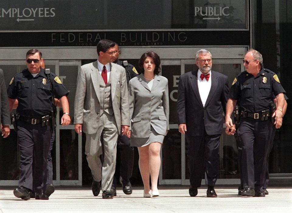 Monica Lewinsky (center) is escorted by police officers, federal Investigators, and her attorney William Ginsburg as she leaves the Federal Building on 28 May 1998 in Westwood, California, after submitting new evidence to Ken Starr's office (VINCE BUCCI/AFP via Getty Images)
