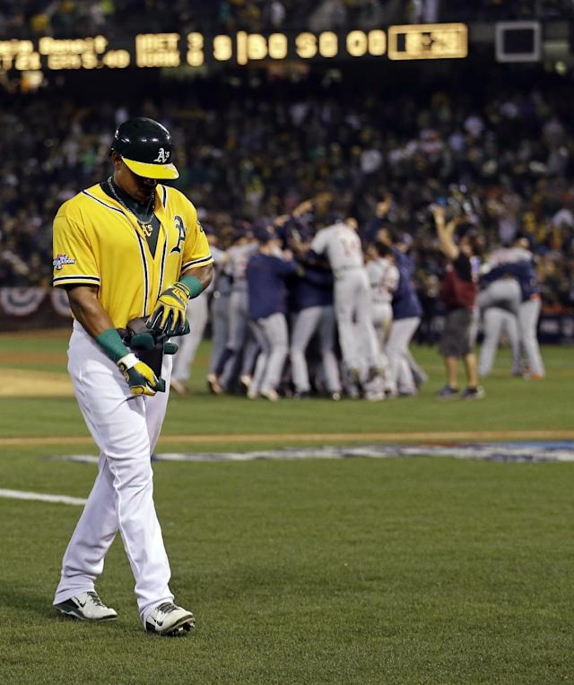 Oakland Athletics left fielder Yoenis Cespedes (52) walks off the field as the Detroit Tigers celebrate in the background after the Tigers beat the A's 3-0 to win Game 5 of an American League baseball division series in Oakland, Calif., Thursday, Oct. 10, 2013. (AP Photo/Marcio Jose Sanchez)