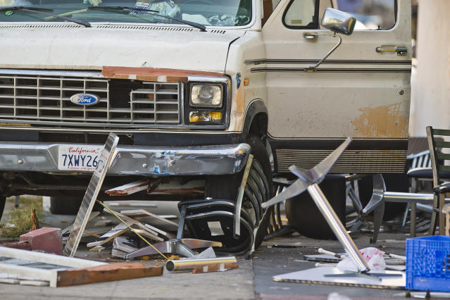 <p>Broken restaurant tables and chairs are seen under a van that plowed into a group of people dining on a Los Angeles sidewalk injuring several Sunday, July 30, 2017. A witness to the crash told The Associated Press the van jumped a curb and careened into a group of people eating outside The Fish Spot restaurant in the city's Mid-Wilshire neighborhood. The cause of the crash is under investigation. (AP Photo/Damian Dovarganes) </p>