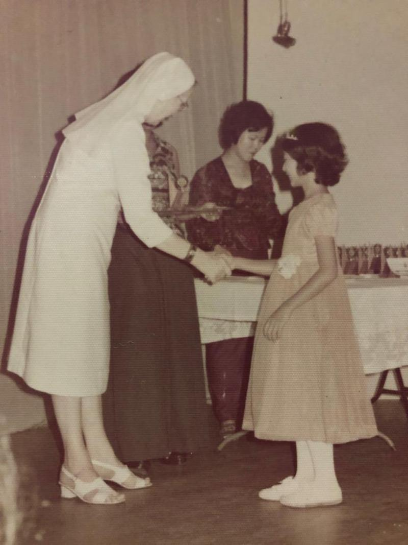 Melinda at age eight receiving a prize from then CLS principal Sister Frances de Sales. — Picture courtesy of Melinda Lim