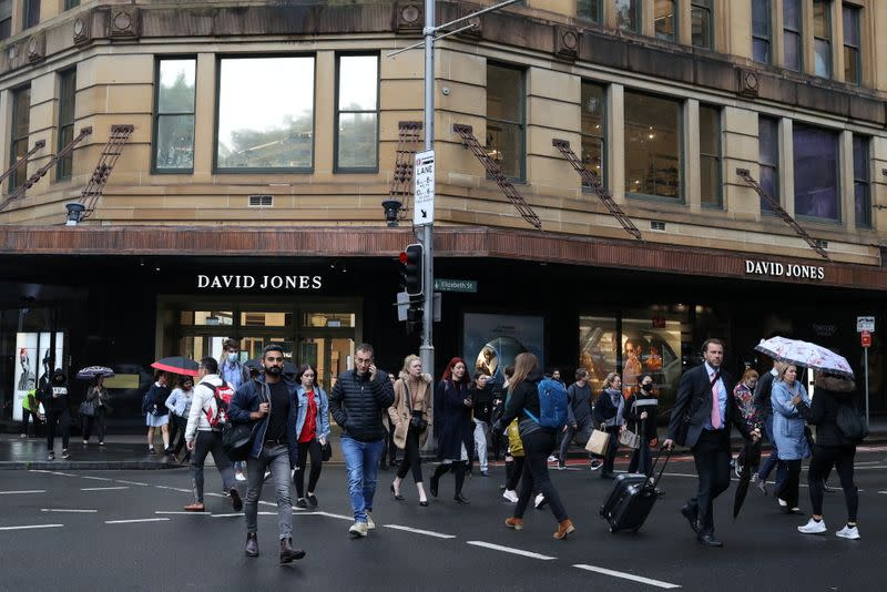 Pedestrians cross a street in the city centre of Sydney