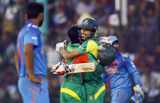 Bangladesh's Mushfiqur Rahim, center left, embraces teammate Nasir Hossain after scoring a century during the Asia Cup one-day international cricket tournament against India in Fatullah, near Dhaka, Bangladesh, Wednesday, Feb. 26, 2014. (AP Photo/A.M. Ahad)