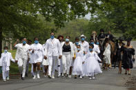 """Iran """"Bang"""" Paylor, center, of Washington, walks with family including his sisters LaShawn Paylor, center left, Sade Paylor, and Colletta Paylor, in front of the horse drawn hearse carrying the casket of their mother, Joanne Paylor, 62, of southwest Washington, to her interment at Lincoln Memorial Cemetery in Suitland-Silver Hill, Md., Sunday, May 3, 2020. The original funeral for Paylor, who the family believes died of a heart attack, was delayed for close to two months while her family hoped social distancing guidelines would be lifted. Despite not having died from coronavirus, almost every aspect of her funeral has been impacted by the pandemic. (AP Photo/Jacquelyn Martin)"""