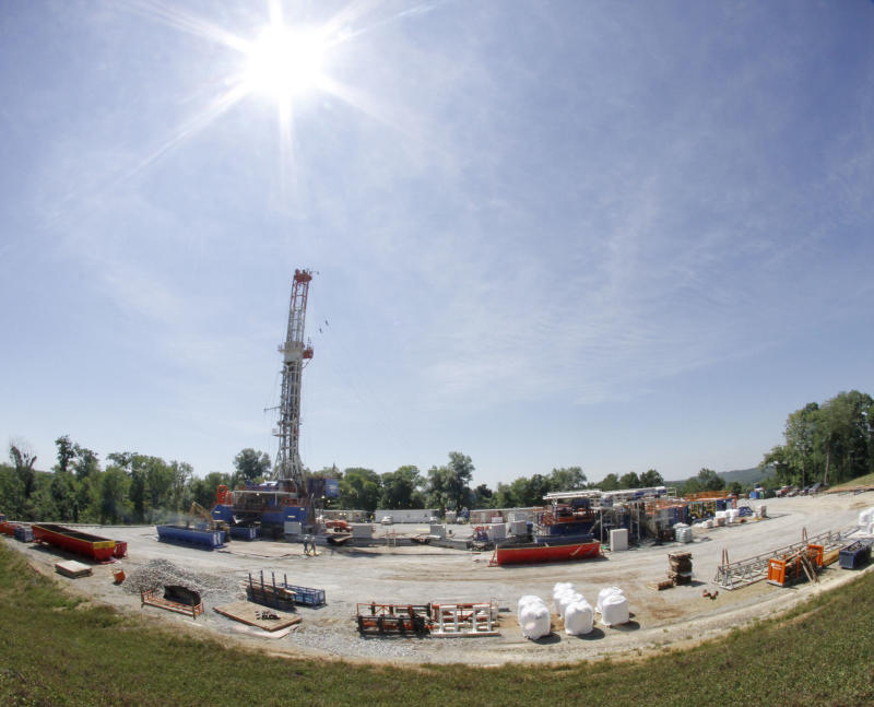 """In this July 27, 2011 photo, the sun shines over a Range Resources well site in Washington, Pa. The company is  one of many drilling into the Marcellus Shale layer deep underground and """"fracking"""" the area to release natural gas. (AP Photo/Keith Srakocic)"""