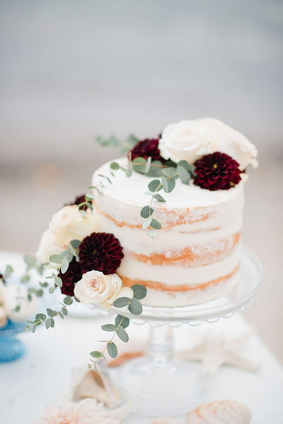 """<p>Deep red and blush blooms paired with fresh eucalyptus dresses up this small fall wedding cake by <a href=""""https://www.kelseyelizabethcakes.com/"""" rel=""""nofollow noopener"""" target=""""_blank"""" data-ylk=""""slk:Kelsey Elizabeth Cakes"""" class=""""link rapid-noclick-resp"""">Kelsey Elizabeth Cakes</a>.</p>"""