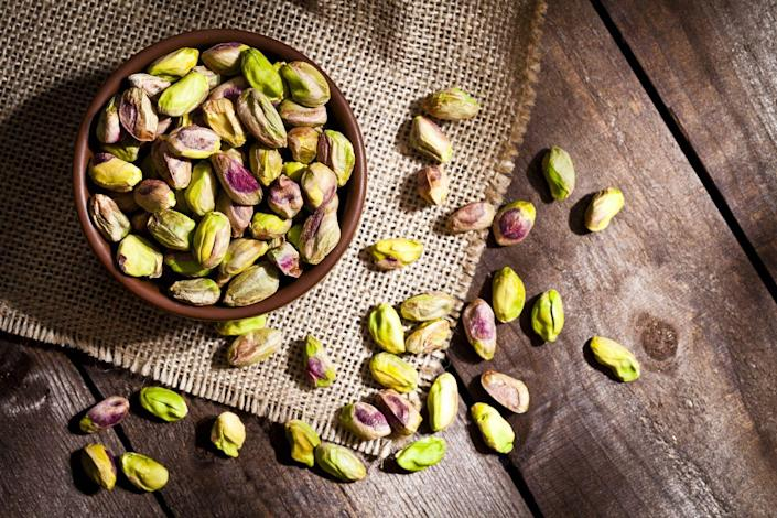 """<p><a href=""""https://www.ncbi.nlm.nih.gov/pubmed/22665124"""" rel=""""nofollow noopener"""" target=""""_blank"""" data-ylk=""""slk:Pistachios"""" class=""""link rapid-noclick-resp"""">Pistachios</a> have been proven to lower blood pressure by reducing blood vessel tightening and heart rate. </p><p><strong>Try it: </strong>Add pistachios to a salad or breakfast cereal. Just be sure to buy unsalted when shopping at the supermarket.<br></p>"""