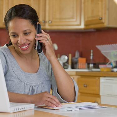 Hispanic-woman-working-on-a-laptop-and-talking-on-a-mobile-phone_web