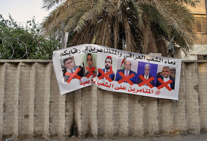 """A poster with defaced pictures of Iraqi politicians and Arabic that reads, """"the blood of the protesters and the Iraqi people is on your necks, the conspirators on the people and the religious authority,"""" in hung on the wall near Tahrir Square during anti-government demonstrations in Baghdad, Iraq, Thursday, Dec. 26, 2019. (AP Photo/Khalid Mohammed)"""