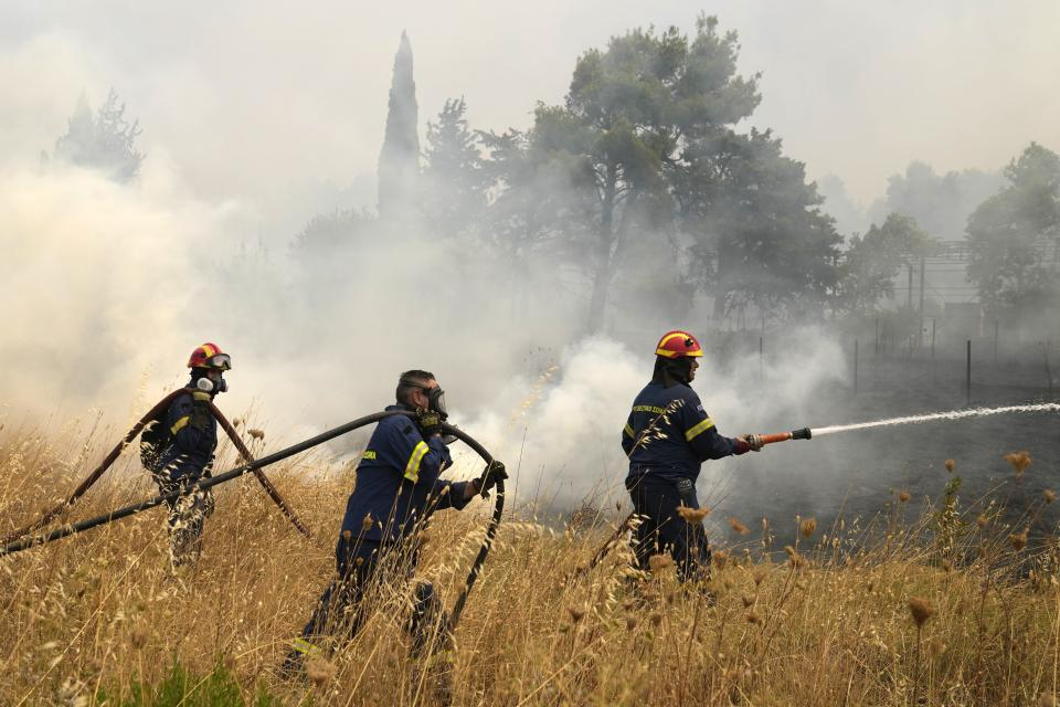 Firefighters try to extinguish a fire in Kapandriti village, about 38 kilometres (23 miles) north of Athens, Greece, Friday, Aug. 6, 2021. Thousands of people fled wildfires burning out of control in Greece and Turkey on Friday, as a protracted heat wave turned forests into tinderboxes and flames threatened populated areas, electricity installations and historic sites. (AP Photo/Thanassis Stavrakis)