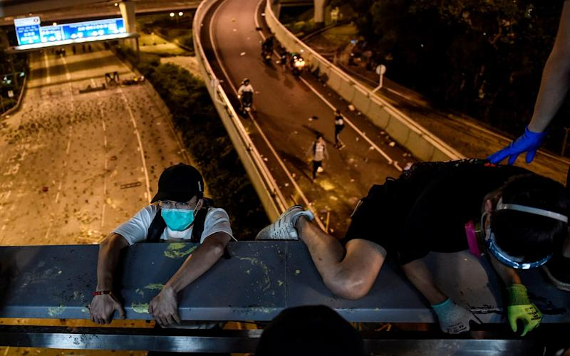Protesters cling onto a bridge as they attempt to escape from the besiegedHong Kong Polytechnic University campus and from police - AFP