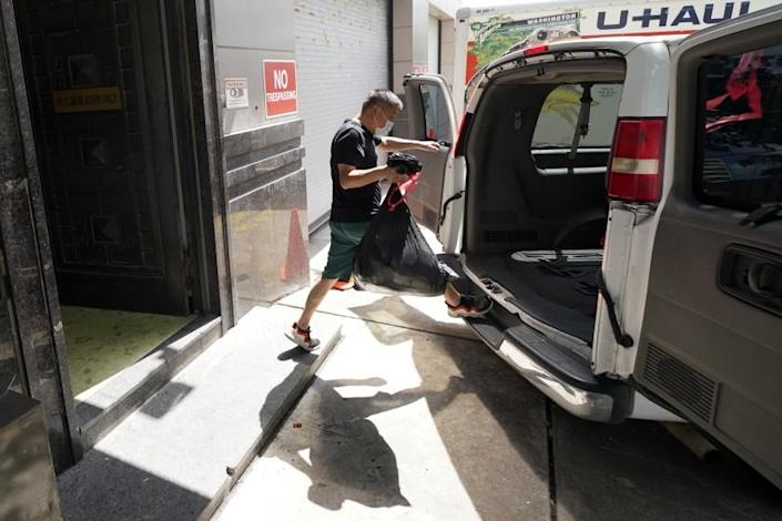 A man loads the back of a van with a bag from inside the Chinese Consulate Thursday, July 23, 2020, in Houston. China says the U.S. has ordered it to close its consulate in Houston in what it called a provocation that violates international law. (AP Photo/David J. Phillip)