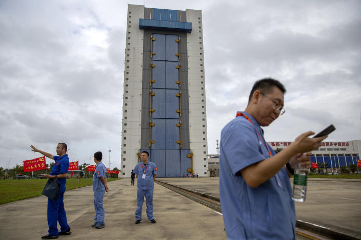 Workers gather near a building at the Wenchang Space Launch Site in Wenchang in southern China's Hainan province, Monday, Nov. 23, 2020. Chinese technicians were making final preparations Monday for a mission to bring back material from the moon's surface for the first time in nearly half a century — an undertaking that could boost human understanding of the moon and of the solar system more generally. (AP Photo/Mark Schiefelbein)