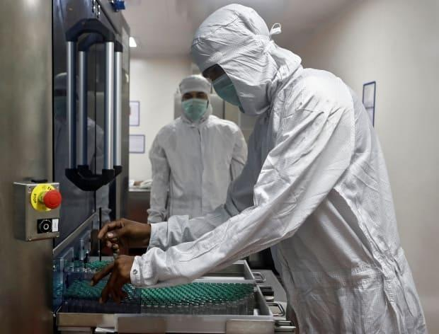 An employee in personal protective equipment (PPE) removes vials of AstraZeneca's COVISHIELD coronavirus disease (COVID-19) vaccine from a visual inspection machine inside a lab at Serum Institute of India, Pune, India, November 30, 2020. (Francis Mascarenhas/Reuters - image credit)