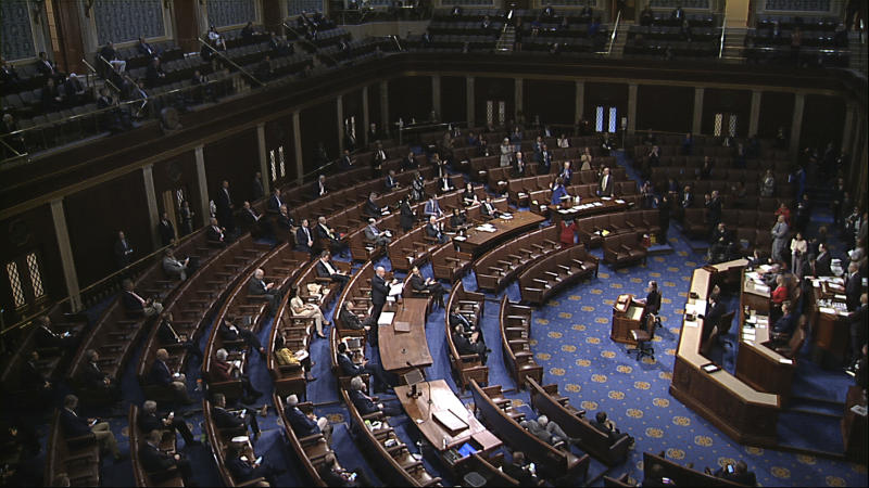 In this image from video, members of the House practice social distancing as they sit on the floor and in the public gallery above during debate on the coronavirus stimulus package on the floor of the House of Representatives at the U.S. Capitol in Washington, Friday, March 27, 2020. (House Television via AP)
