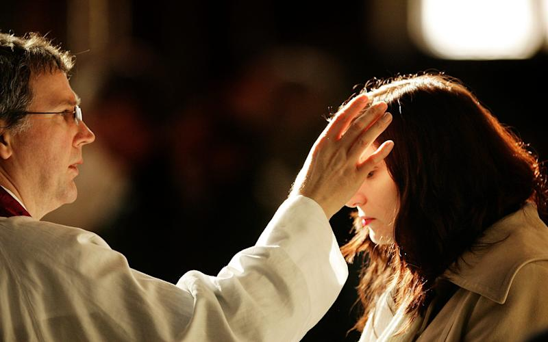 A churchgoer receives a cross of ashes painted on her forehead from a priest during Ash Wednesday Mass at Westminster Cathedral - Getty Images