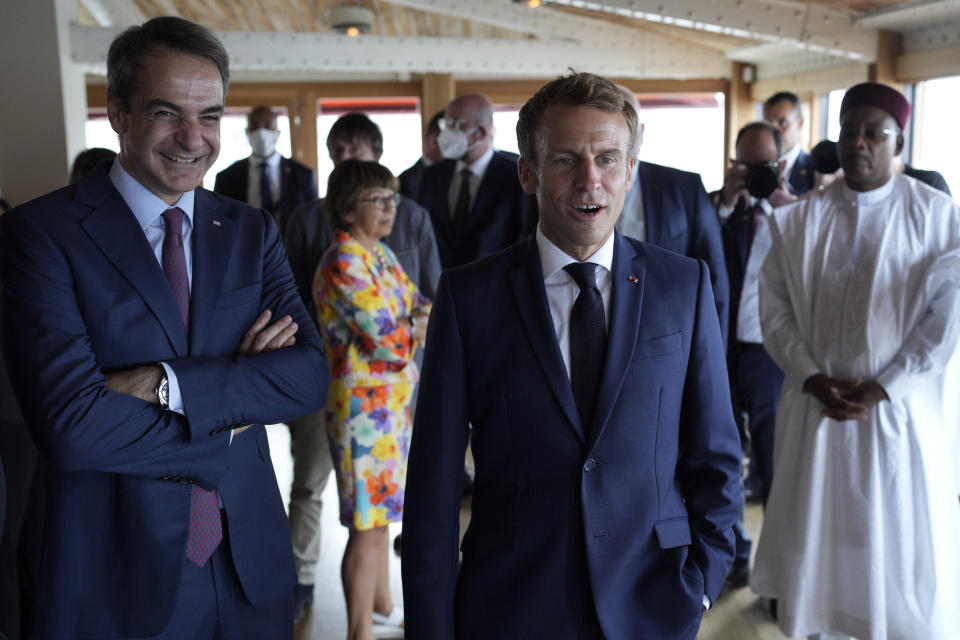 French President Emmanuel Macron, right, and Greek Prime Minister Kyriakos Mitsotakis arrive for a lunch in Peron restaurant on the Corniche Kennedy, in Marseille, southern France, Friday Sept. 3, 2021. Macron is expected to urge the world to better protect biodiversity as key to fight climate change and support human welfare at a global summit starting Friday in southern France. (AP Photo/Daniel Cole, pool)