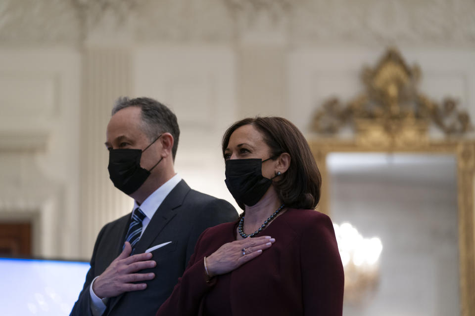 Vice President Kamala Harris, and her husband Doug Emhoff, place their hands over their hearts during a performance of the national anthem, during a virtual Presidential Inaugural Prayer Service, in the State Dinning Room of the White House, Thursday, Jan. 21, 2021, in Washington. (AP Photo/Alex Brandon)