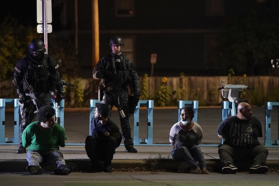 Police hold four people on the street Friday, Oct. 9, 2020, in Wauwatosa, Wis. On Wednesday, District Attorney John Chisholm refused to issue charges against Wauwatosa Police Officer Joseph Mensah for the Feb. 2 fatal shooting of 17-year-old Alvin Cole at Mayfair Mall. (AP Photo/Morry Gash)