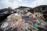 Debris piles up at curbside as residents gut their flooded homes in the aftermath of Hurricane Ida in LaPlace, La., Tuesday, Sept. 7, 2021. (AP Photo/Gerald Herbert)