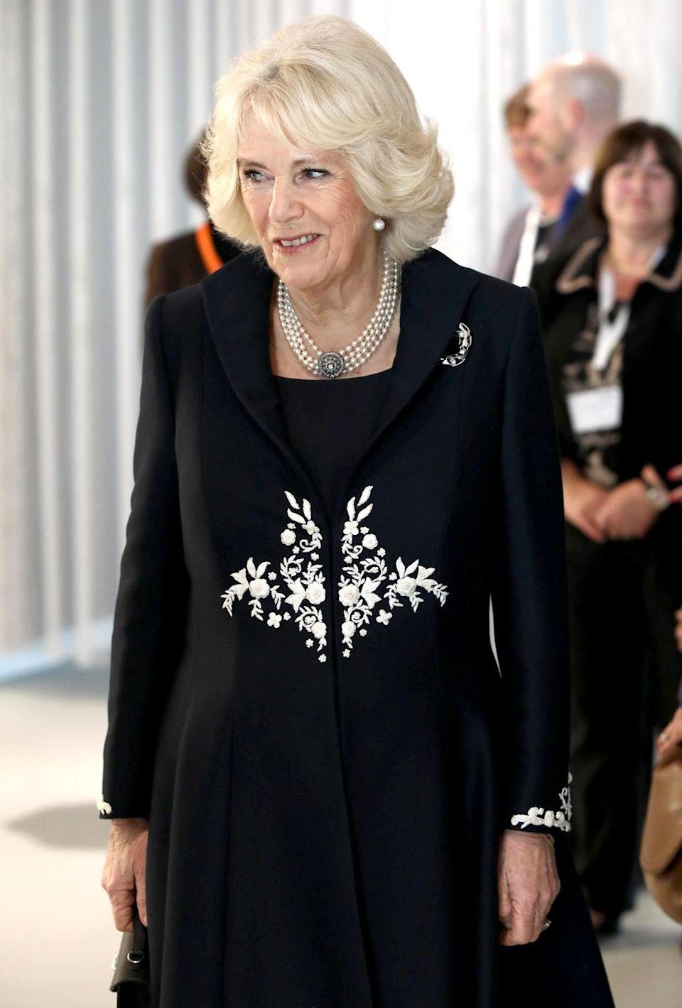 <p>Camilla wore an embroidered black coat, pearl earrings, a pearl choker, and diamond broach to attend the launch of the Royal Osteoporosis Society. </p>