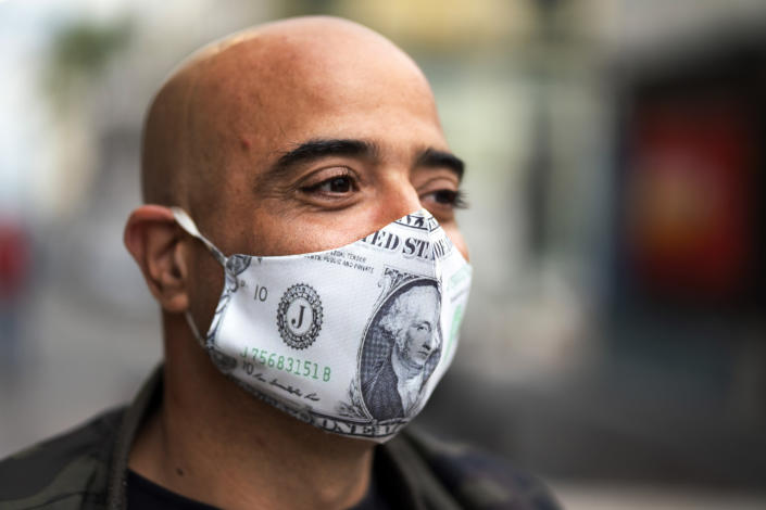 A man whose mask features U.S. dollar bills stands in line for free food from residents helping others facing economic hardship amid the lockdown to contain the spread of COVID-19 in the financial district of Montevideo, Uruguay, Saturday, April 25, 2020. (AP Photo/Matilde Campodonico)