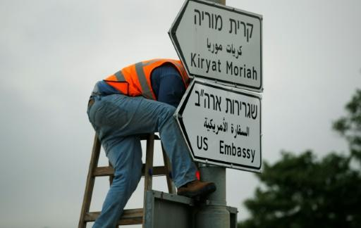 A worker puts up a road sign indicating the way to the new US embassy in Jerusalem on May 7, 2018