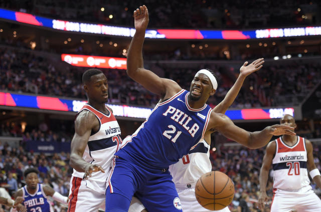 "<a class=""link rapid-noclick-resp"" href=""/nba/teams/was/"" data-ylk=""slk:Washington Wizards"">Washington Wizards</a> center <a class=""link rapid-noclick-resp"" href=""/nba/players/3954/"" data-ylk=""slk:Ian Mahinmi"">Ian Mahinmi</a>, left, fouls <a class=""link rapid-noclick-resp"" href=""/nba/teams/phi/"" data-ylk=""slk:Philadelphia 76ers"">Philadelphia 76ers</a> center <a class=""link rapid-noclick-resp"" href=""/nba/players/5294/"" data-ylk=""slk:Joel Embiid"">Joel Embiid</a> (21) during the first half of an NBA basketball game, Wednesday, Oct. 18, 2017, in Washington. (AP Photo/Nick Wass)"