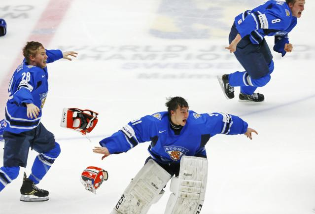 Finland's goalie Juuse Saros (C), Artturi Lehkonen (L) and Saku Maenlanen celebrate after defeating Sweden in overtime of their IIHF World Junior Championship gold medal ice hockey game in Malmo, Sweden, January 5, 2014. REUTERS/Alexander Demianchuk (SWEDEN - Tags: SPORT ICE HOCKEY)