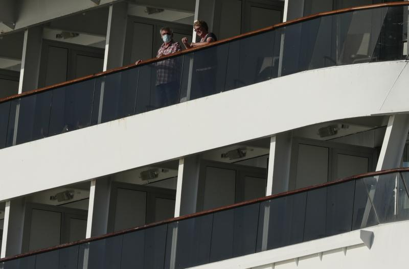 Passengers, one wearing a protective face mask, look out from the Zaandam cruise ship, anchored in the bay of Panama City, Friday, March 27, 2020. Several passengers have died aboard the cruise ship and a few people aboard the ship have tested positive for the new coronavirus, the cruise line said Friday, with hundreds of passengers unsure how long they will remain at sea. (AP Photo/Arnulfo Franco)