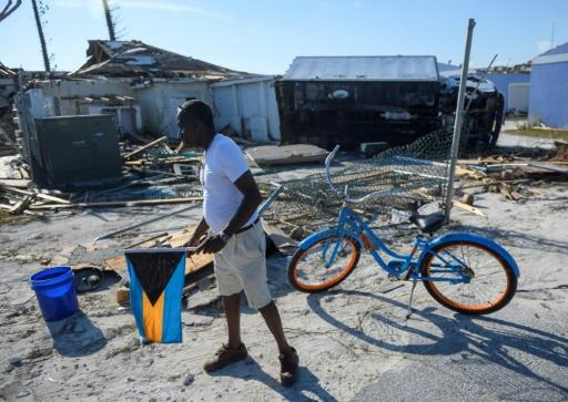 Irvin Russell carries the Bahamian flag as he walks past a damaged truck on Treasure Cay in the hurricane-hit Bahamas