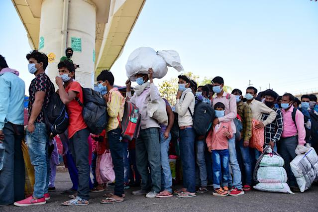 DELHI, INDIA - 2020/03/29: Migrant workers queue at Anand vihar bus terminal, wearing face masks as a preventive measure during the nationwide lock down. The Indian government imposed a 21 day nationwide lock down as a preventive measure against the corona virus pandemic. (Photo by Manish rajput/SOPA Images/LightRocket via Getty Images)