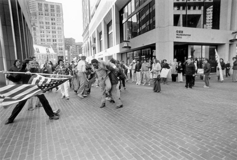 """""""The Soiling of Old Glory"""" A white teenager, Joseph Rakes, is about to assault black lawyer and civil rights activist Ted Landsmark with a flagpole bearing the American flag. The photograph was taken in Boston on April 5, 1976, during a protest against court-ordered desegregation busing. The photo won the1977 Pulitzer Prize for Spot Photography. (Photo: Stanley Forman/stanleyformanphotos.com)"""