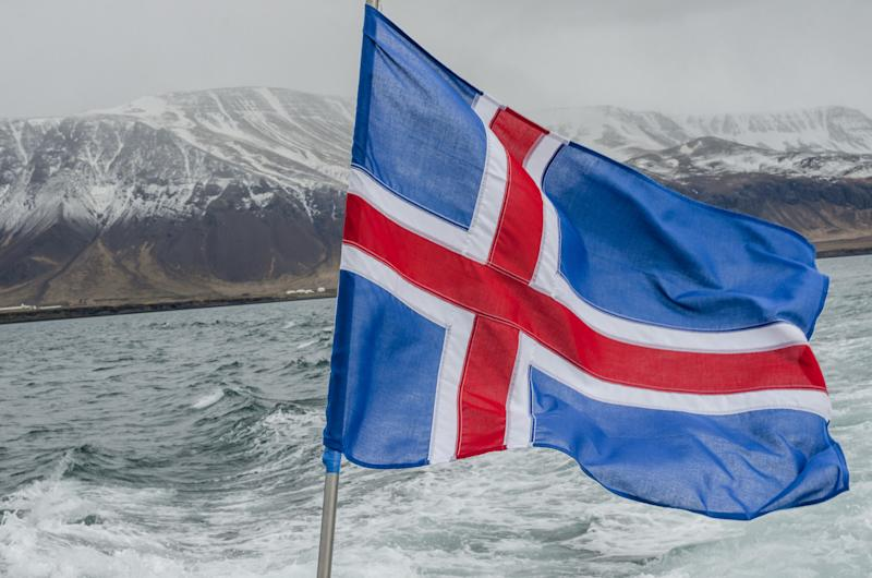 Cold day on Atlantic Ocean boat with misty mountains and Icelandic flag in foreground