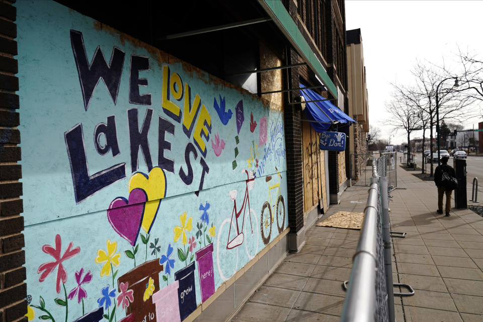 "A person walks past a mural with ""We love Lake St"" on the side of a building March 22, 2021, in Minneapolis. Nearly a year after sometimes violent protests for racial justice shook Minneapolis, the immigrant corridor is struggling to recover. Lake Street, the focus of much violence during the protests that followed George Floyd's death in police custody, has been a beacon for immigrants for more than a century. (AP Photo/Jim Mone)"