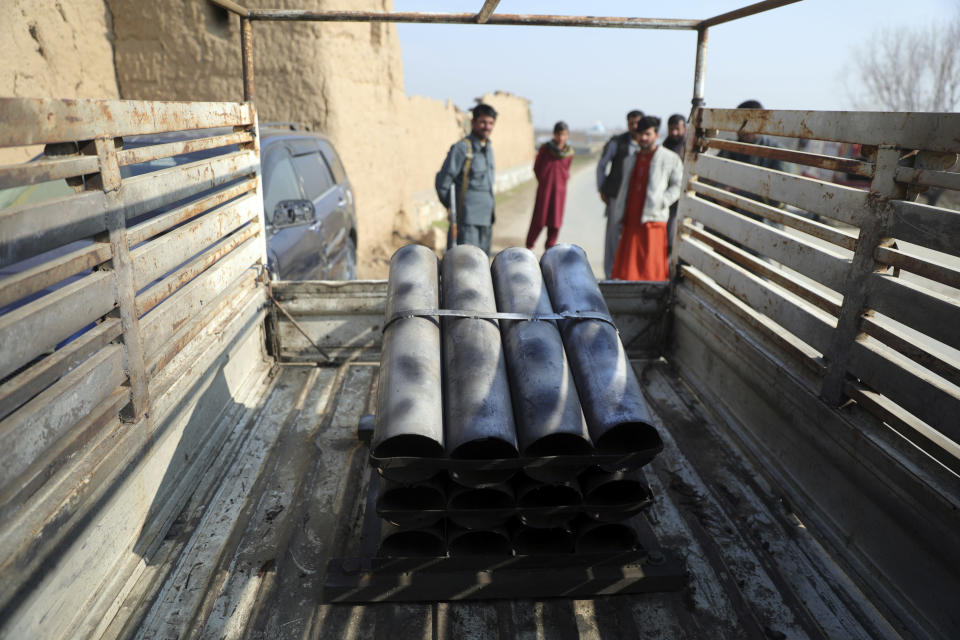 Afghan security personnel stand near a vehicle in which rockets were placed in Bagram, north of Kabul, Afghanistan, Saturday, Dec. 19, 2020. Five rockets were fired at a major U.S. base in Afghanistan on Saturday, but there were no casualties, NATO and provincial officials said. (AP Photo/Rahmat Gul)