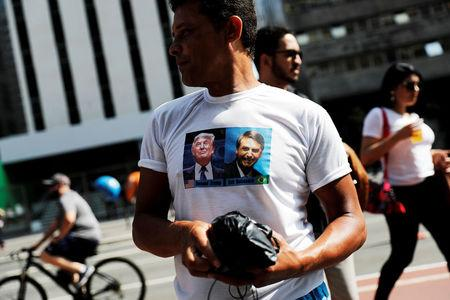 FILE PHOTO: A supporter wears a T-shirt with the images of presidential candidate Jair Bolsonaro and U.S. President Donald Trump at Paulista Avenue after Bolsonaro was stabbed in Juiz de Fora, in Sao Paulo