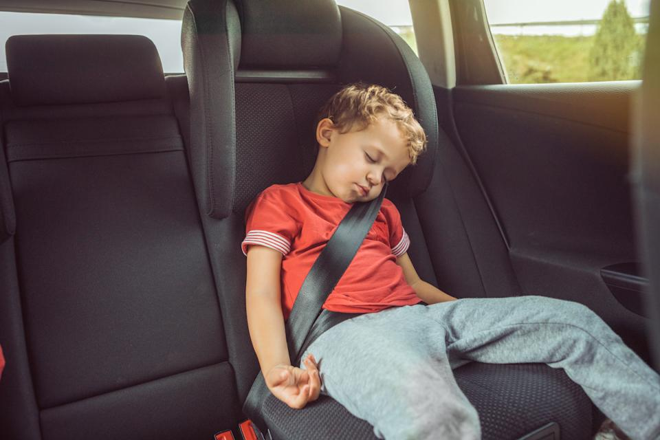 Child asleep in car booster seat as parents are warned about dangers of improper car restraints.