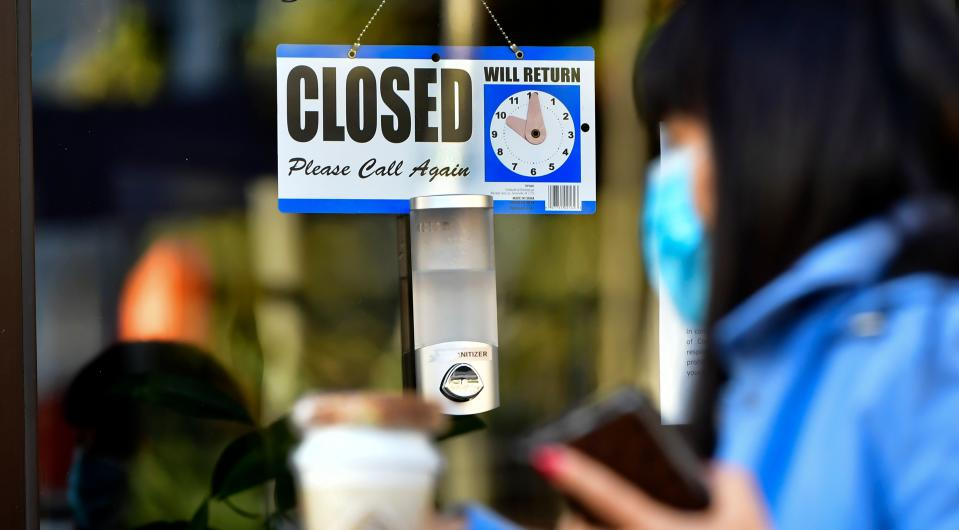A pedestrian wearing her facemask and holding a cup of coffee walks past a Closed sign hanging on the door of a small business in Los Angeles, California on November 30, 2020. - Los Angeles County's new stay-at-home restrictions took effect on November 30, 2020, one day after the county reported more than 5,000 new COVID-19 cases. (Photo by Frederic J. BROWN / AFP) (Photo by FREDERIC J. BROWN/AFP via Getty Images)