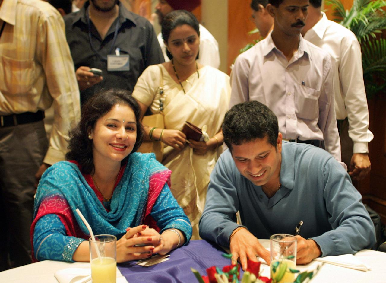 MUMBAI, INDIA:  Indian cricketer Sachin Tendulkar (R) along with his wife Anjali (L) signs autographs for customers during an interaction with lucky customers of the recently launched TVS Victor Edge and Star motor cycles in Mumbai,  06 October 2005.  Tendulkar gave away TVS motor-cycles to 24 lucky customers.  The company recorded the highest ever sales of two wheelers and motor cycles during the month of September 2005.   AFP PHOTO/Sebastian D'SOUZA.  (Photo credit should read SEBASTIAN D'SOUZA/AFP/Getty Images)
